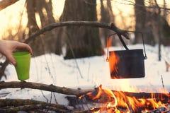Ein Topf im Feuer, Wasser wird im Winterwald erhitzt Lizenzfreies Stockfoto