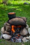 Ein Topf Lebensmittel an der Stange Ofen von den Steinen Lizenzfreie Stockfotografie