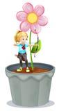 Ein Topf mit einer Blume und einem Mädchen an der Spitze Lizenzfreies Stockfoto