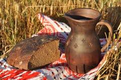 Ein Topf von Milch und von halben Laib des Roggenbrotes Lizenzfreies Stockbild
