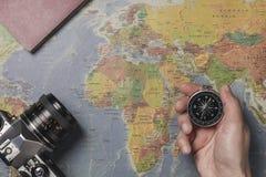 Ein Tourist, der einen Kompass, ihre Ferien planend hält Mit einigen Pässen und einer Kamera auf der Karte der Welt stockbilder
