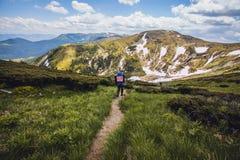 Ein Tourist geht entlang eine Gebirgsschlängelnde Spur Lizenzfreies Stockfoto