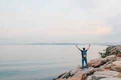 Ein Tourist mit einem Rucksack auf der Küste Reise, Tourismus, Erholung Stockfotografie