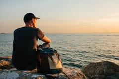 Ein Tourist mit einem Rucksack auf der Küste Reise, Tourismus, Erholung Auf dem Sonnenuntergang Lizenzfreie Stockfotografie