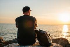 Ein Tourist mit einem Rucksack auf der Küste Reise, Tourismus, Erholung Auf dem Sonnenuntergang Lizenzfreies Stockbild
