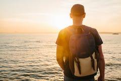Ein Tourist mit einem Rucksack auf der Küste Reise, Tourismus, Erholung Auf dem Sonnenuntergang Stockbilder