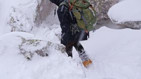 Ein Tourist mit einem Rucksack auf seinen Schultern steigt von der Spitze eines schneebedeckten Berges ab stock video