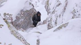 Ein Tourist mit einem Rucksack auf seinen Schultern steigt von der Spitze eines schneebedeckten Berges ab stock footage