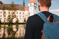 Ein Tourist mit einem Rucksack betrachtet den Anblick Das Schloss, das Blatna in der Tschechischen Republik genannt wird, wird in Stockfotografie