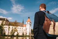 Ein Tourist mit einem Rucksack betrachtet den Anblick Das Schloss, das Blatna in der Tschechischen Republik genannt wird, wird in Stockbild