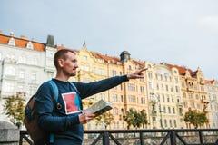 Ein Tourist mit einem Rucksack vor einer schönen alten Architektur in Prag in der Tschechischen Republik Er betrachtet die Karte stockfoto