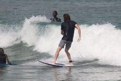 Ein Tourist soll in, Lagos-Strand zu surfen genießen, während zwei Bewunderer aufpassen stockbild