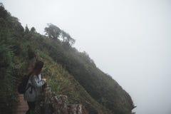 Ein touristisches Gehen und ein Trekking der Frau entlang den Bergen im tropischen Wald stockbild