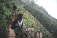 Ein touristisches Gehen und ein Trekking der Frau entlang den Bergen im tropischen Wald lizenzfreie stockbilder