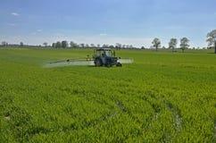 Ein Traktor, der das Feld sprüht stockfotos