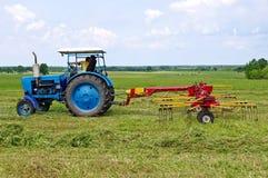Ein Traktor, der geschnittenes Heu dreht Lizenzfreie Stockfotos