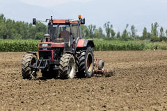 Ein Traktor, der Weizen auf den fruchtbaren Bauernhofgebieten von G pflanzend arbeitet Stockbilder