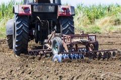 Ein Traktor, der Weizen auf den fruchtbaren Bauernhofgebieten von G pflanzend arbeitet Lizenzfreie Stockfotografie