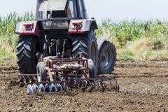 Ein Traktor, der Weizen auf den fruchtbaren Bauernhofgebieten von G pflanzend arbeitet Lizenzfreies Stockfoto