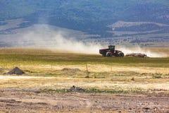 Ein Traktor im Abstand, der oben Staub tritt Stockbilder