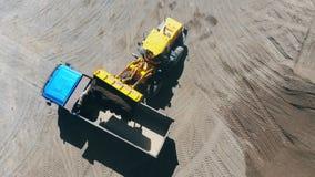 Ein Traktor lädt einen großen LKW mit zerquetschten Steinen stock video footage