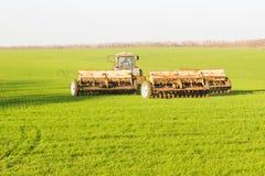 Ein Traktor mit der geschleppten landwirtschaftlichen Maschinerie, die an dem Feld arbeitet stockfotografie