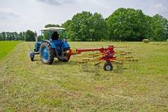Ein Traktor und ein geschnittenes Heu Lizenzfreie Stockfotografie
