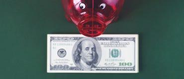 Ein transparentes Schweinsparschwein auf einem Hintergrund von Rechnungen von Dollar stockfotos