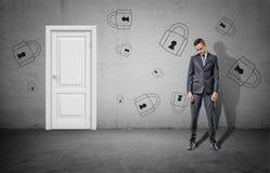 Ein trauriger Geschäftsmann mit seinem Kopftief steht nahe einer geschlossenen weißen Tür und einer Betonmauer mit vielen gezogen Stockbilder