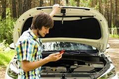 Ein trauriger Mann wartet auf Hilfe und nennt den Beistandsservice, weil sein Auto aufgliederte Stockfoto