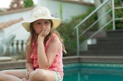 Ein trauriges, deprimiertes kleines Mädchen in einem Hut, der nahe einem Pool sitzt Lizenzfreie Stockfotografie