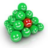 Ein trauriges deprimiertes Stirnrunzeln-Gesicht in vielen lächelnden Gesichtern Lizenzfreie Stockfotos