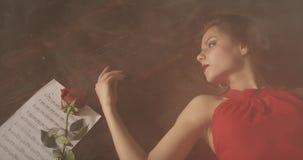 Ein trauriges Mädchen mit den roten Lippen liegt auf dem dunklen Boden im Rauche stock footage
