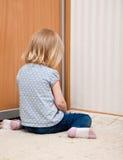 Ein trauriges Mädchen sitzt auf dem Fußboden lizenzfreie stockfotos