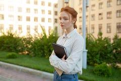 Ein trauriges rothaariges Mädchen mit Sommersprossen auf ihrem Gesicht hält einen Ordner in ihren Händen lizenzfreies stockfoto