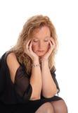Ein trauriges schauendes blondes Frauensitzen Lizenzfreies Stockfoto