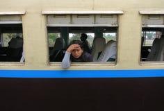 Ein trauriges und müdes birmanisches Mädchen, das aus dem Fenster eines alten Zugs heraus schaut lizenzfreie stockfotos