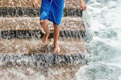 Ein Treppenhaus f?r Badeg?ste im Atlantik, ein junger Mann, der hinunter die Treppe springt lizenzfreies stockbild