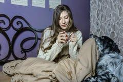 Ein trinkender Kaffee des Mädchens im Bett und Spielen mit ihrem Hund Stockfotos