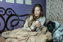 Ein trinkender Kaffee des Mädchens im Bett und Spielen mit ihrem Hund Lizenzfreie Stockbilder