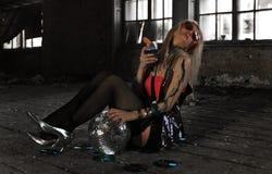 Ein trinkendes Cocktail des Mädchens an verlassenem Haus Stockfoto