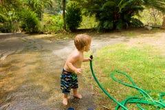 Ein Trinkwasser des Kleinkindes von einem Schlauch Stockfoto