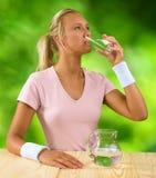 Ein Trinkwasser des Mädchens vom Glas Lizenzfreies Stockbild