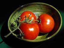 Ein Trio von reifen roten Tomaten auf der Rebe in einer japanischen Tonwaren-Schüssel Lizenzfreies Stockfoto
