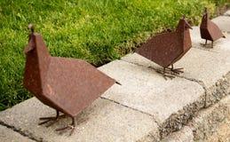 Ein Trio von verrosteten Metallvögeln Lizenzfreie Stockbilder