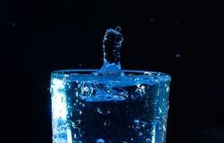 Ein Tropfen eines Glases Wassers in Form einer Faust Stockbild