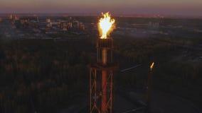 Ein Turm mit einer Fackel auf einer Erdölraffinerie unter dem Holz bei Sonnenuntergang Schattenbild des kauernden Geschäftsmannes stock video
