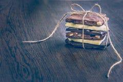 Ein Turm von den Schokoriegeln eingewickelt wie ein Schokoladengeschenk Verschiedene Schokoladenstücke über dunklem hölzernem Hin Lizenzfreies Stockfoto