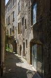 Ein typischer schmaler Durchgang in der Stadt von Montelimar in Frankreich mit hohen Steingebäuden, Eingängen und dunklen Schatte Stockfotos
