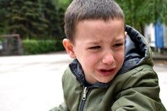 Ein umgekippter Junge, mit Gesicht in Tränen wegen der Schwierigkeiten mit dem Lernen, ein Fahrrad zu reiten lizenzfreies stockbild